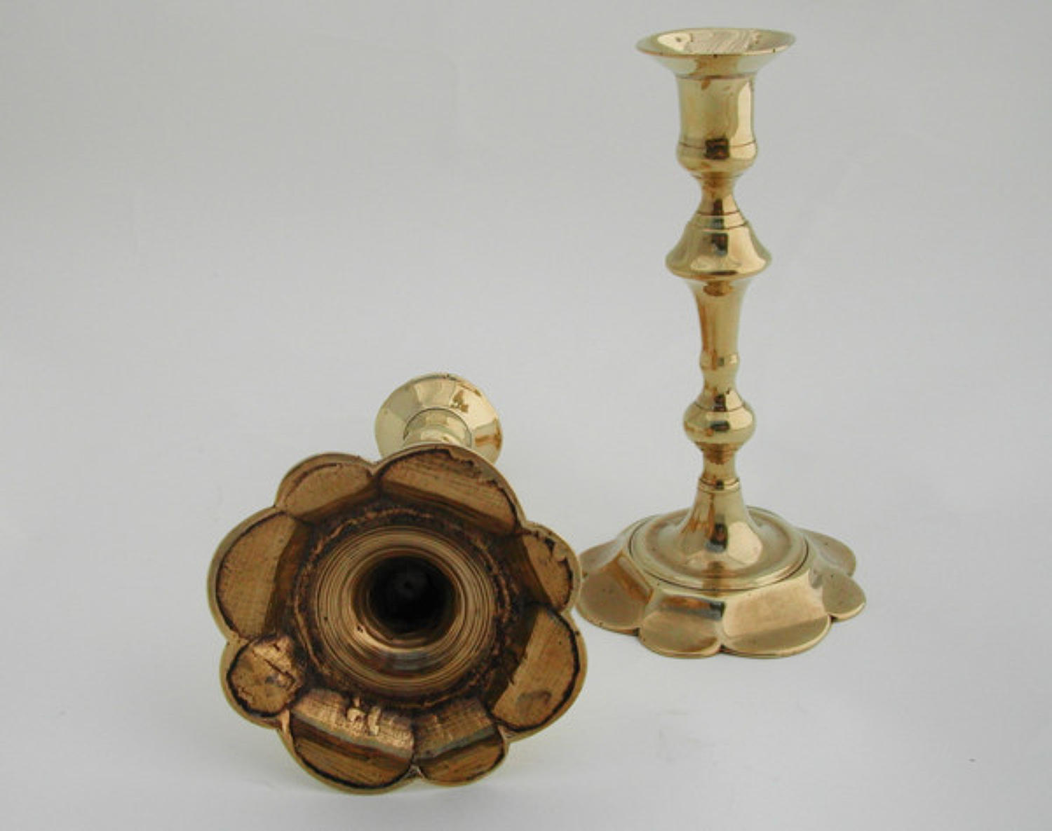 A pair of 18thc Brass petal base Candlesticks. English C1745 - 65